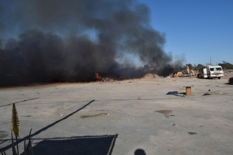 An asphalt lot is filled with fire and smoke. An RV is seen off to the side.