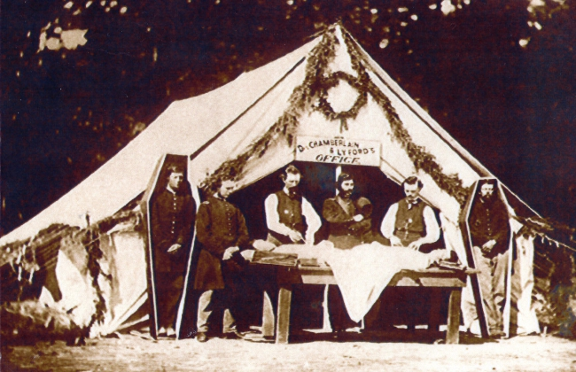 Sepia toned photo from the Civil War Era of four men standing between a large white tent and a wooden table with a white fabric wrapped corpse on top of it. On either sides of the men are two corpses standing in their coffins. There is a sign above them that reads,