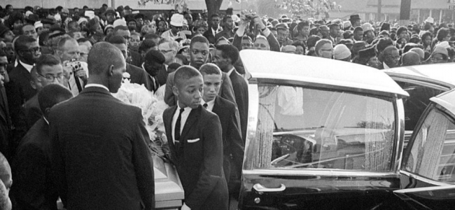 Black and White photo of young Black men carrying a casket into a funeral hearse.